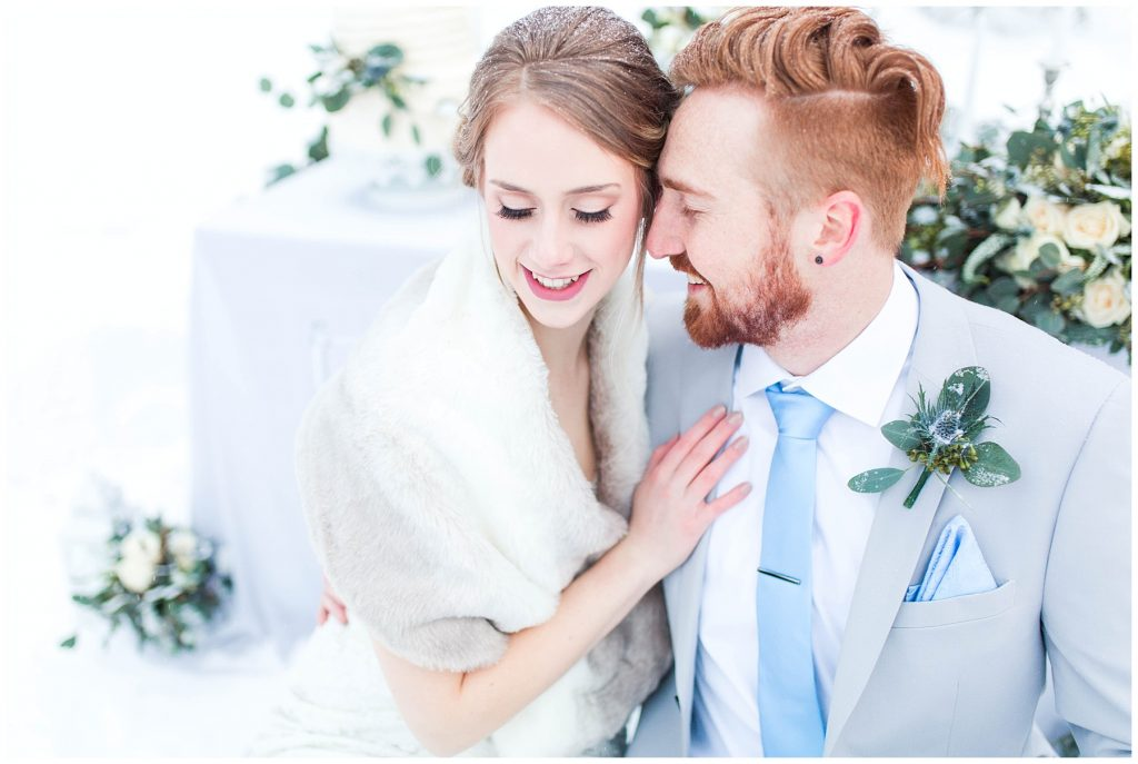 romantic elegant photo of the bride and groom eyes closed close up in grande prairie wedding photographer by kayla lynn photography in the snow by kayla lynn photography bride and groom so happy and smiling