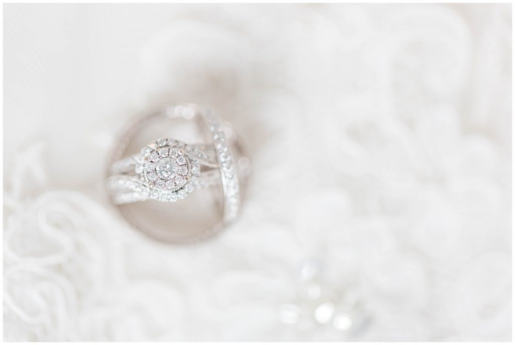 pretty ring photos sitting on wedding dress detail with a light and airy look