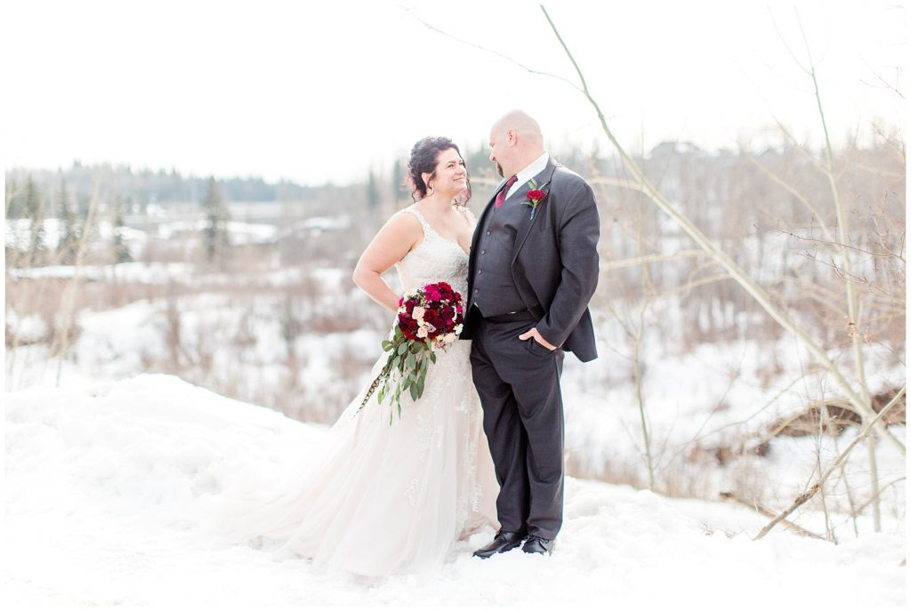 paul and lise bride and groom nose to nose with her red bouquet made from bling out parties in the outdoors in the winter at the bear creek
