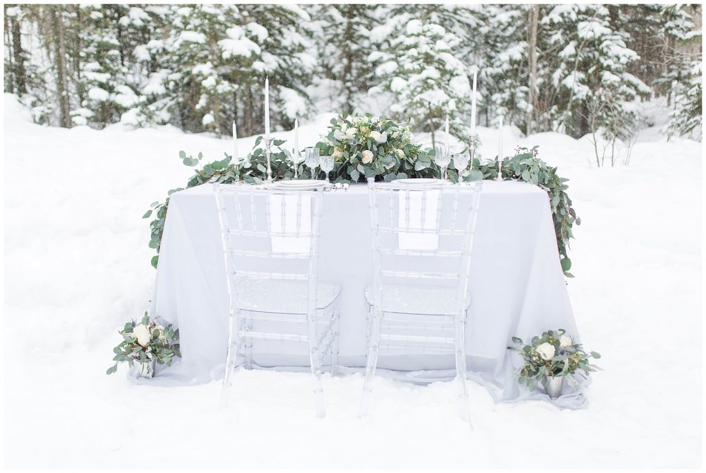 gorgeous winter wedding table set and event rentals surrounded by spruce trees by changing dreams to reality in grande prairie. there is lots of snow for this styled outdoor shoot
