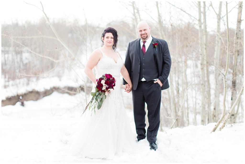 bride and groom holding hands outside in grande prairie in the snow winter time for their wedding day photos