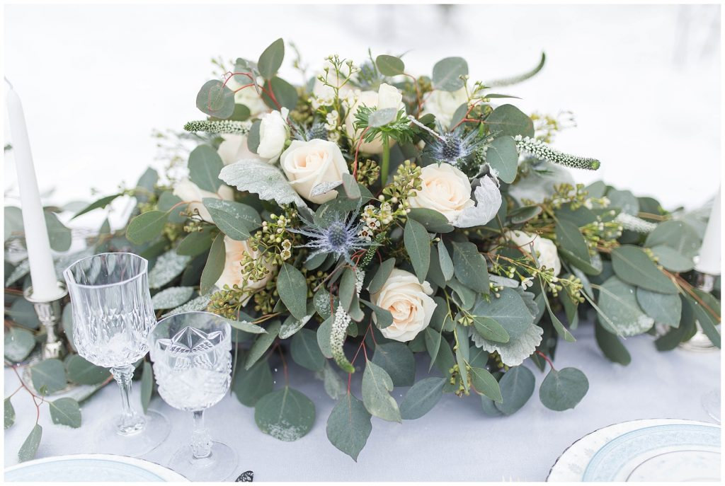 pretty greenery with flowers centerpiece made by the enchanting bouquet outdoor for a winter styled shoot. the bouquet consist of blue thistle, silver dollar, white roses and more.