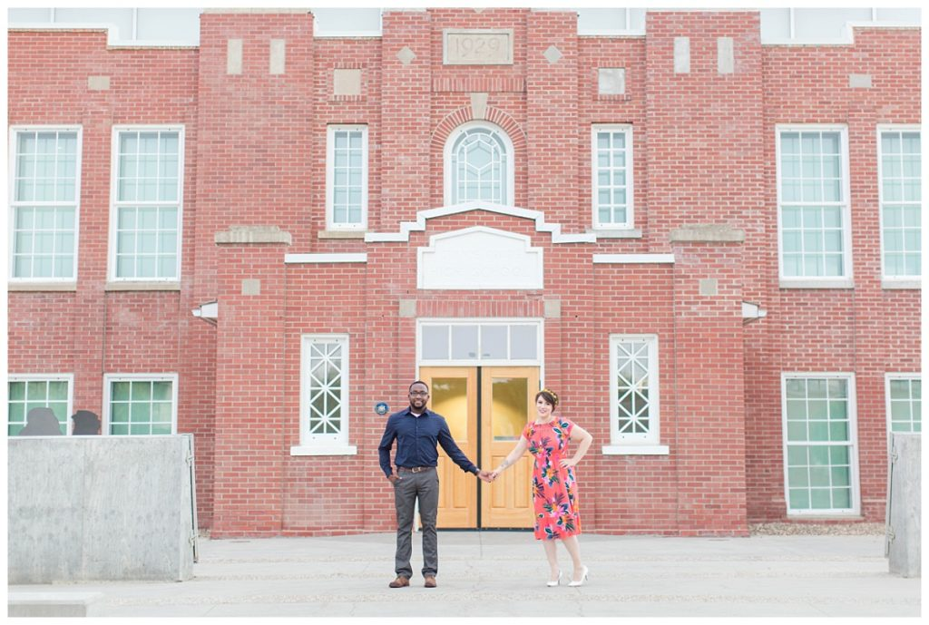 coupole holding hands in grande prairie in front of brick building grande prairie public library