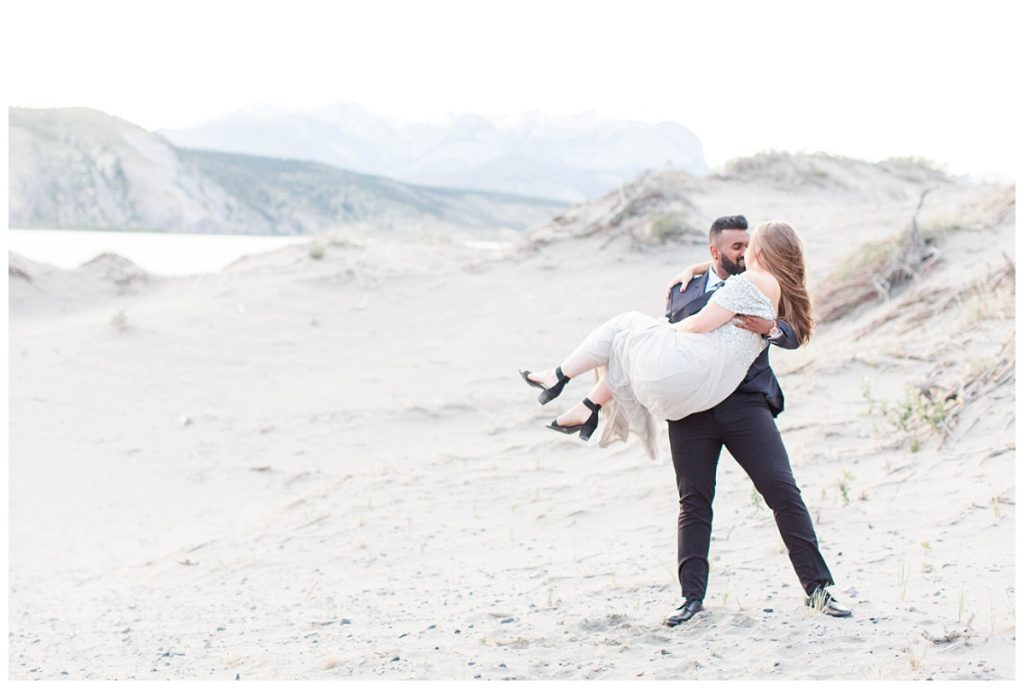 romantic couple groom pick up bride with sand and mountains in the background