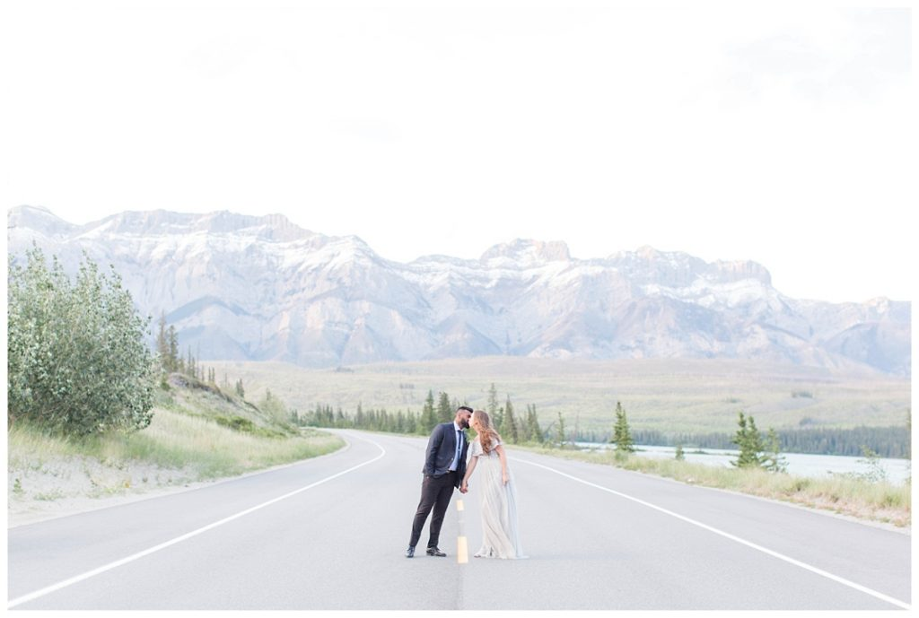 couple kissing on the road in jasper moutains in background