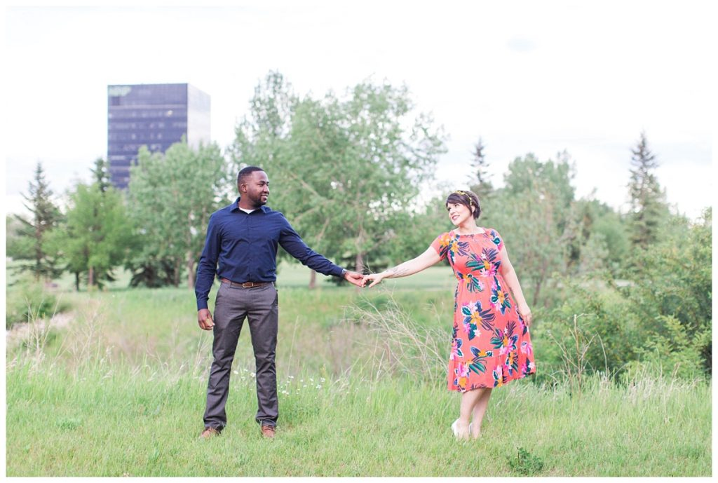 couple holding hands for their engagement photos in front of the 214 place in grande prairie at muskoseepi park kayla lynn photography