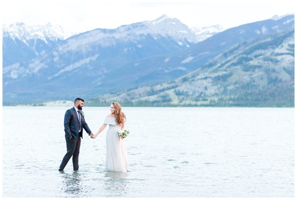 couple walking in the water in jasper lake with mountains for their engagement wedding or elopement photos