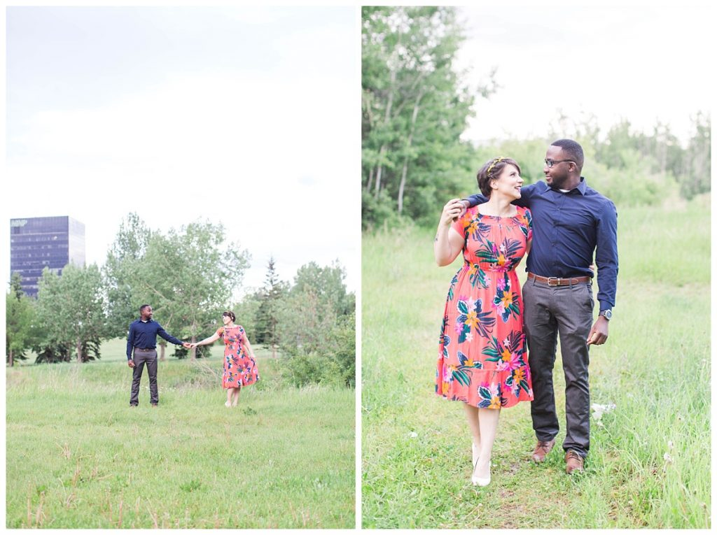 wide shot of couple walking for their engagement photos in front of the 214 place in grande prairie