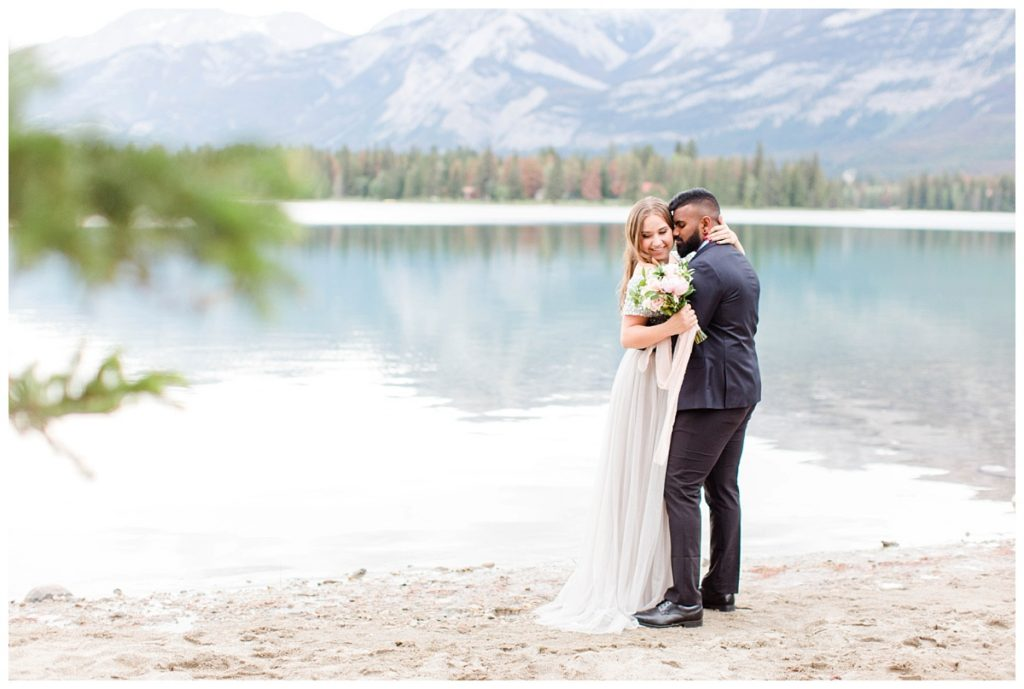 couple in fancy attire at lake annette for their engagement photos in jasper