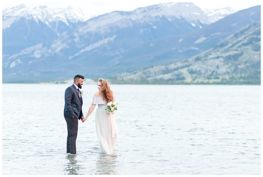 couple walking in jasper lake with mountains in the background wearing suit and light grey dress windy day elopement photography