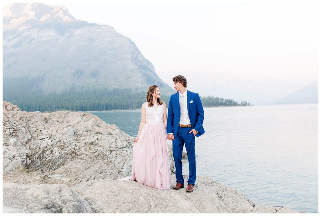cute couple taking engagement photos with photographer wedding in banff and jasper at lake minnewanka