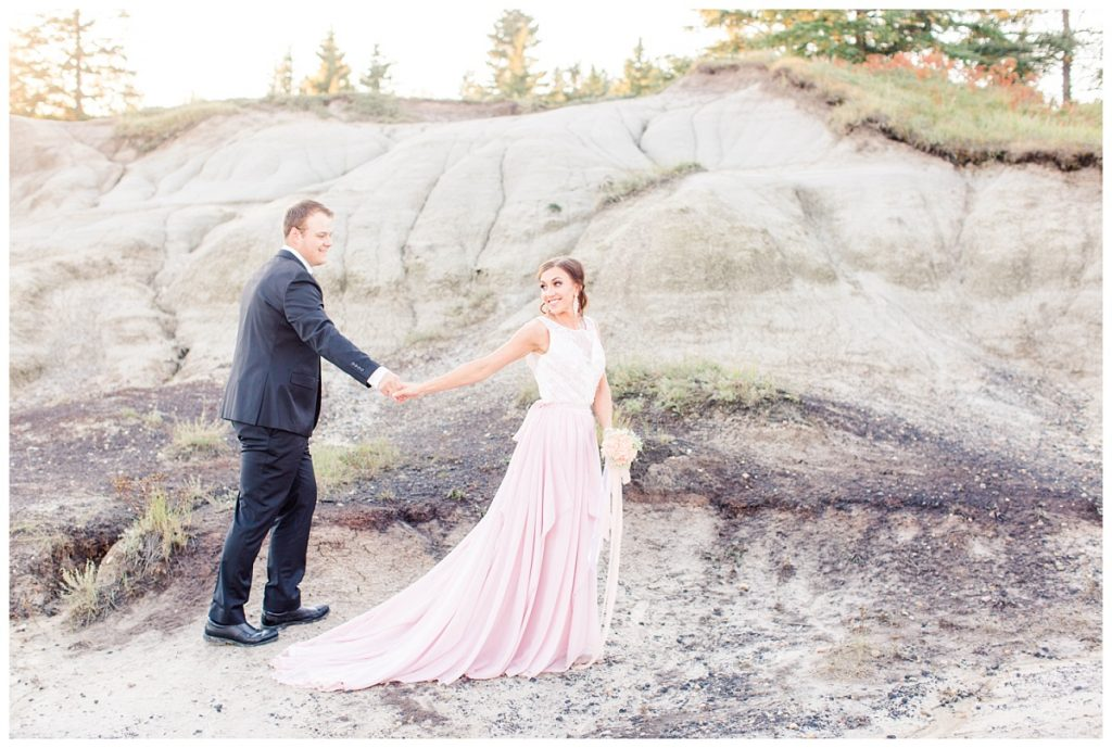 bride and groom walking at kleskun hills in beautiful clothing black tux and blush pink dress smiling
