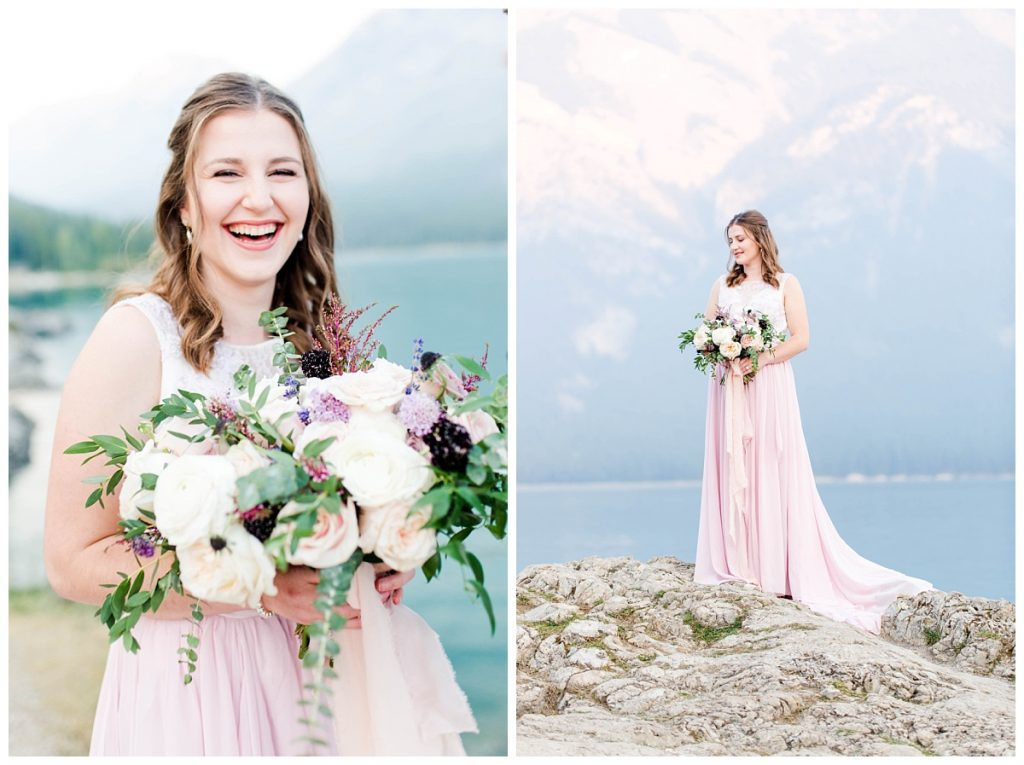 happy bride with her wedding flwoers by wild magnolia floral and blush pink dress in the mountains at lake minnewanka photographer grande prairie