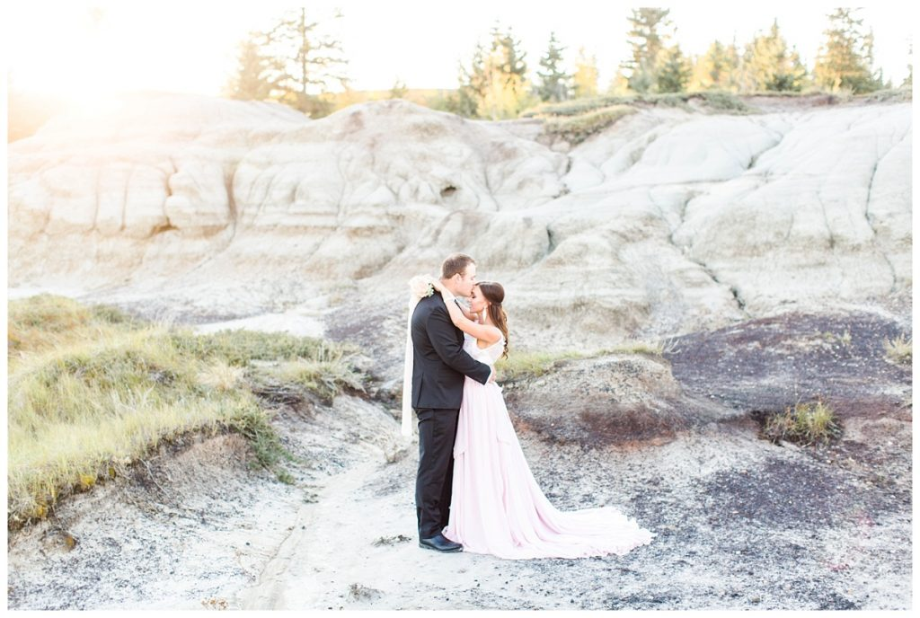 wide angle photo for engagement photos in the badlands in alberta kleskun hills with small bouquet and kissing her