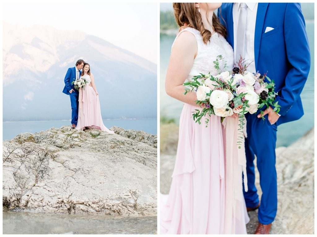 beautiful photographer engagement photos in banff at lake minnewanka with romantic couple blush pink dress and a beautiful mountain backdrop with light rocks in canada best places for photos