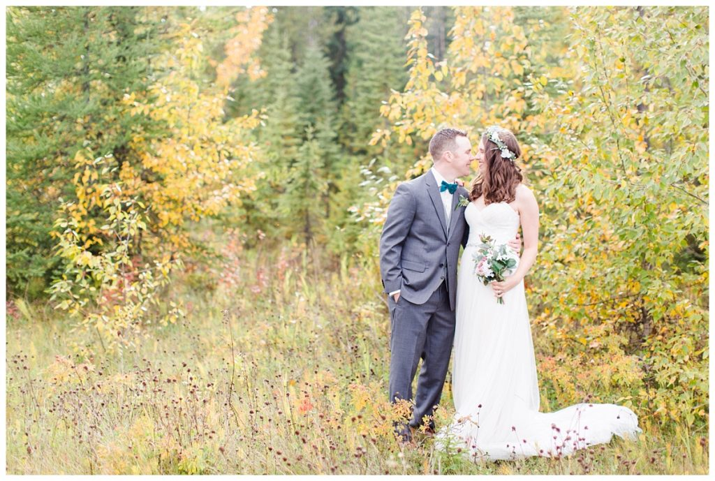 bride and groom in the colorful fall trees in grande prairie