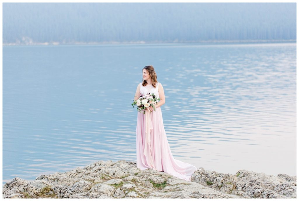 lake minnewanka bridal photo with flowers wild magnolia floral on light rock and full dress blush chiffon mountain backdrop