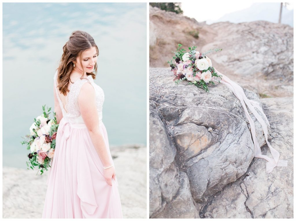romantic couple photo with blush pink dress and wedding flowers at lake minnewanka sitting on rock by wild magnolia flower based in calgary and banff photos