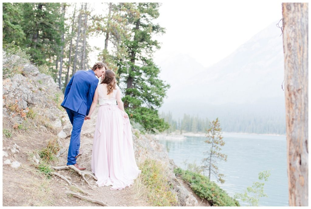 couple in the mountains for engagement alberta photographer kissing at minnewanka lake
