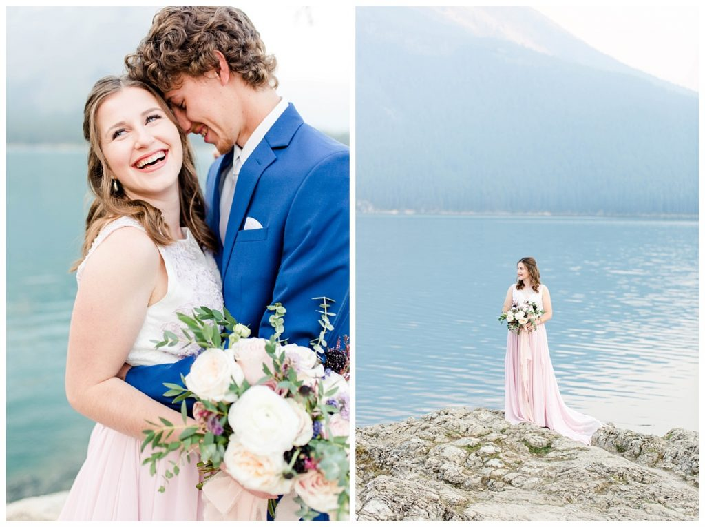 elegant wedding engagement photo at lake minnewanka with couple on the rock bride wearing blush pink dress and groom navy suit next to the mountains and the rocks