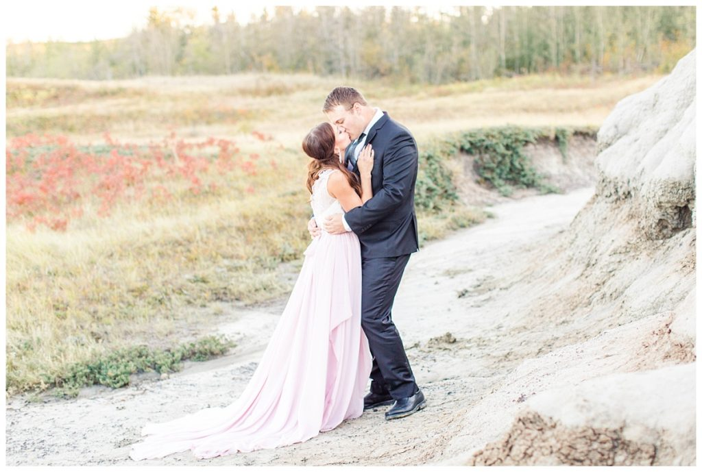 bride and groom kissing at kleskun hills for their engagement wedding photos wearing blush pink chiffon dress and black suit