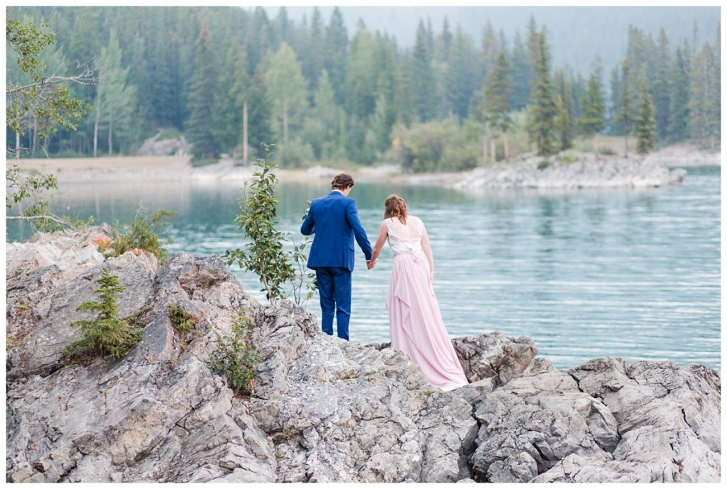 lake minnewanka banff engagement photos couple standing and walking on the rocks with fancy and classy outfits for photos