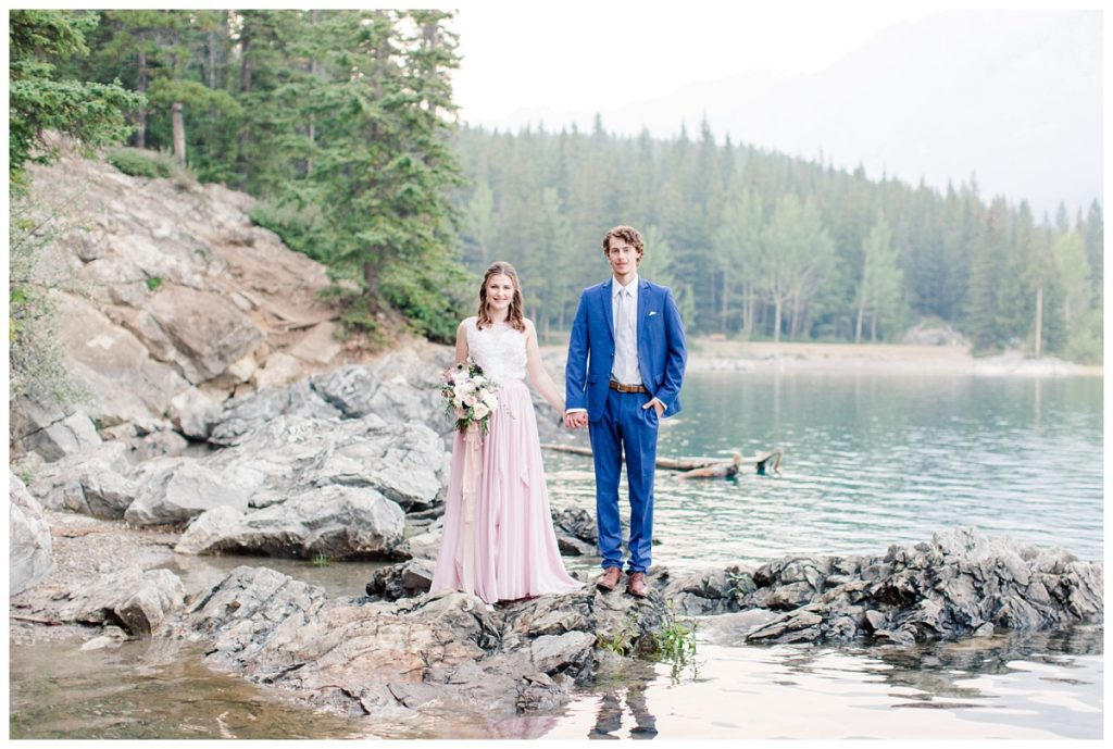 shauna ands james standing on the rocks at lake minnewanka for their anniversary and engagement photos wearing classy elegant chiffon blush dress and navy blue suit in the mountains in banff and jasper