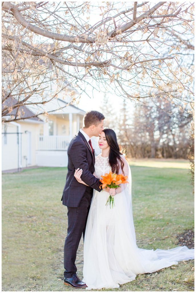 grande prairie wedding photographer in fairview alberta bride with orange wedding flowers with fall trees and victorian house in the background