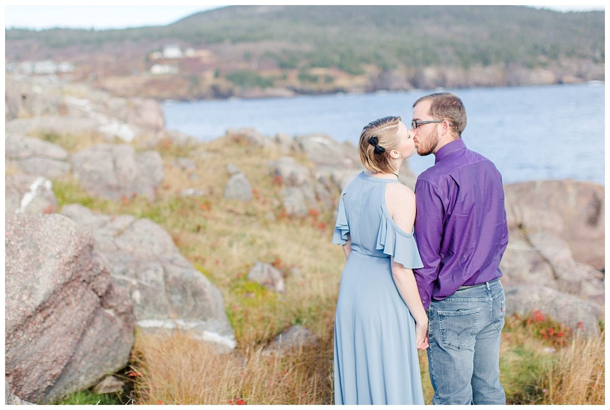 engagement canadian photographer close up kissing with big rocks in the background elegant Newfoundland in canada