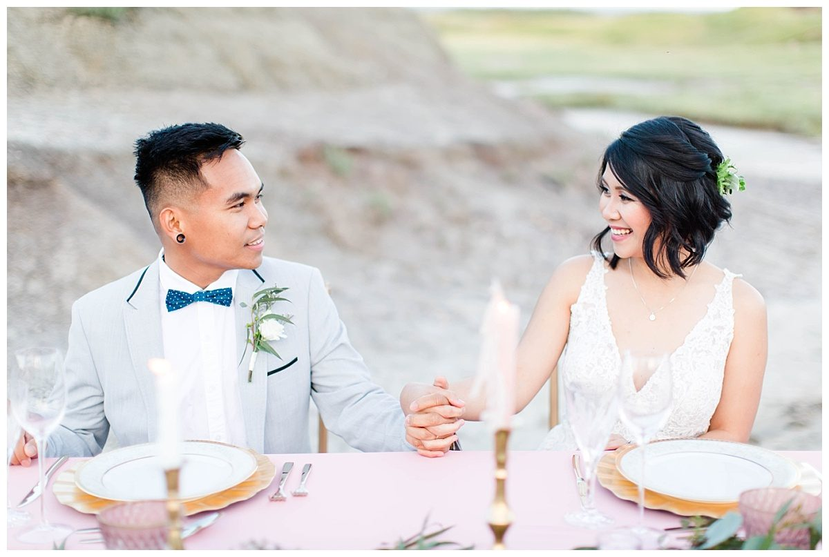 ade and rex sitting at table smiling and holding hands with plates with blush pink decor and gold accents