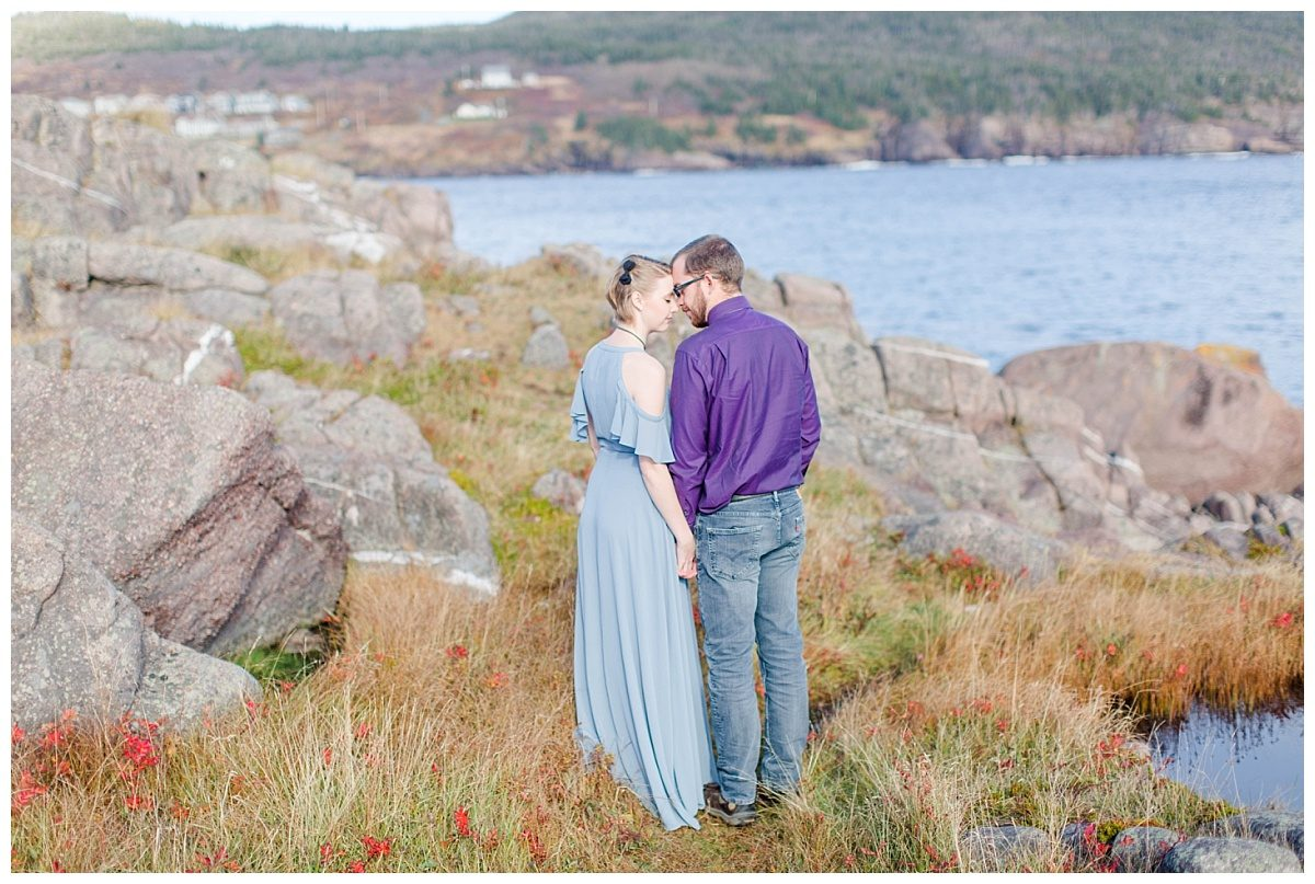 couple nose to nose in newfoundland with lots of rocks and red grass in the fall near the ocean blue and purple maxi dress photographer alberta