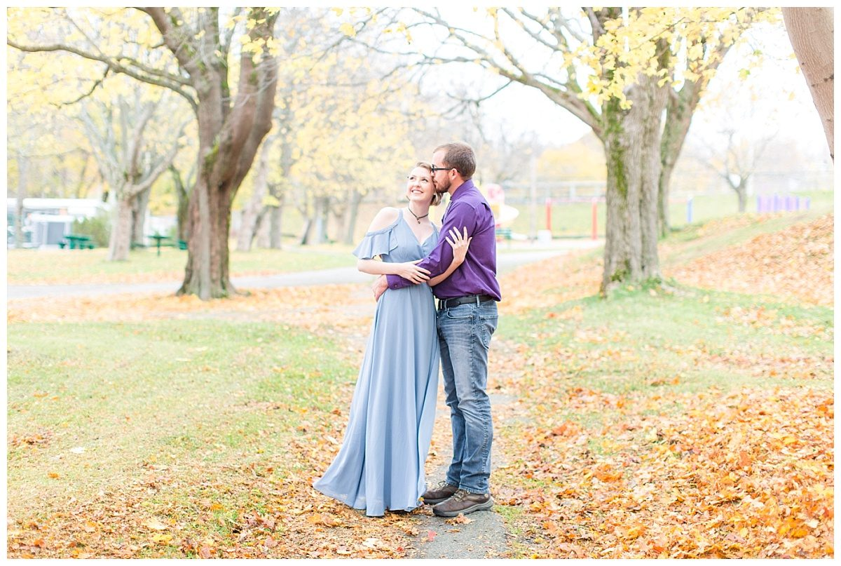 couple engagement photos in the fall with red and orange leaves on the ground in the newfoundland st johns park