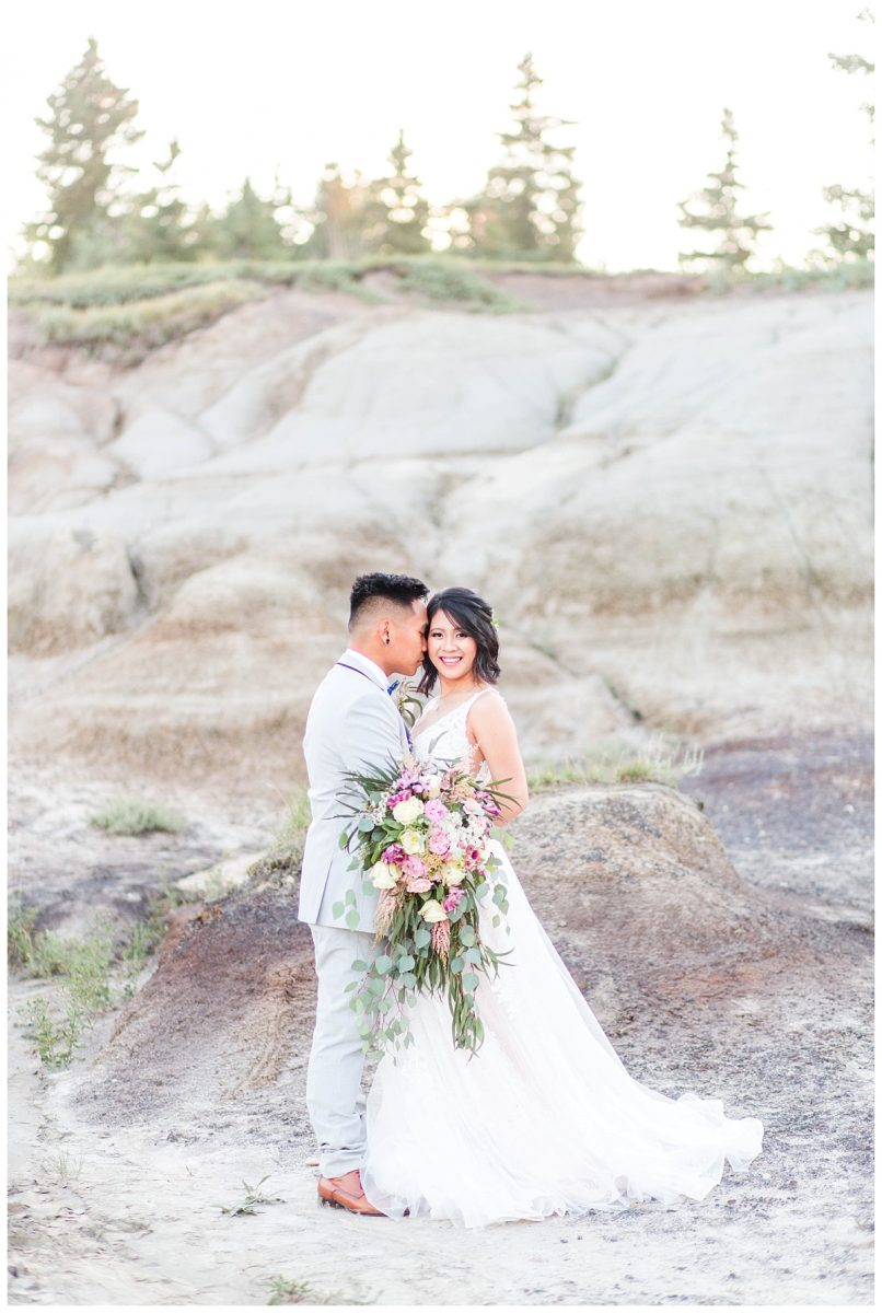 grande prairie elopement photography with jade and rex at kleskun hills with big bridal bouquet in alberta and dress from castaspella