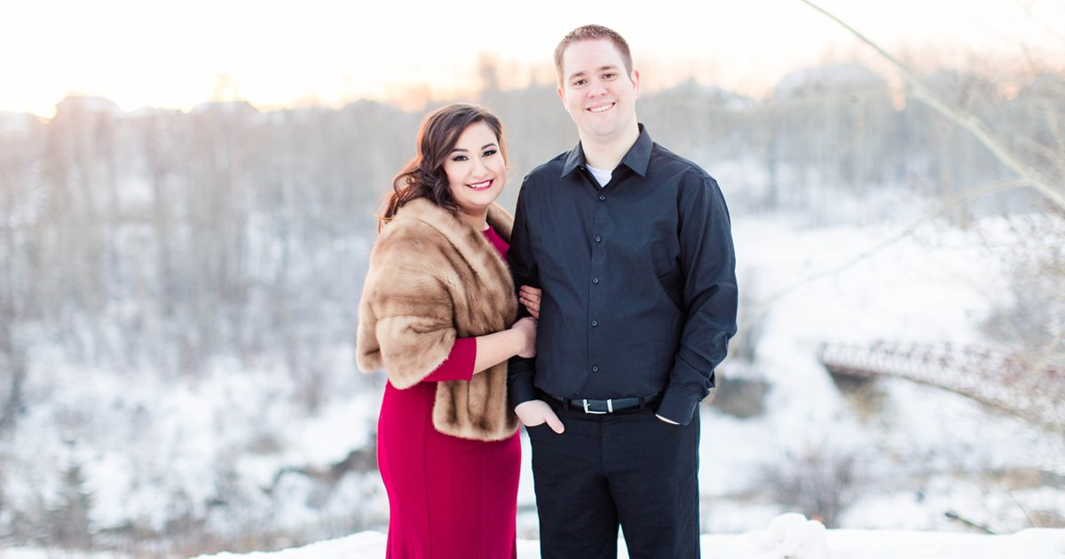 grande prairie couple for their wedding and engagement photographer wearing red dress and smiling at the camera close up photo beautiful