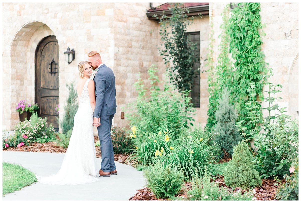 mark and janaya in italy tuscany with their destination wedding photographer bride wearing white dress and light brick wall in the background. vines and lots of greenery surrounds them as they stand on a path. canada