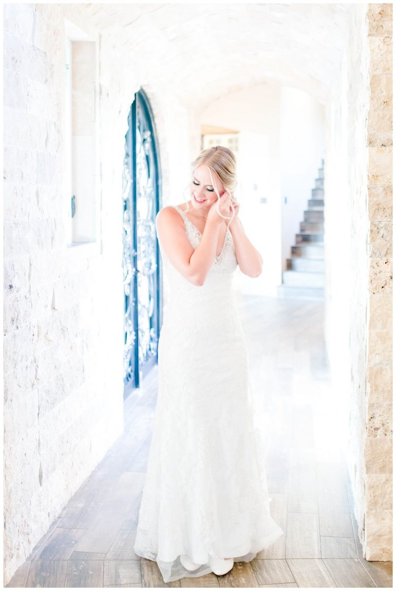 bride getting ready indoor tuscany italy building with her wedding dress earrings