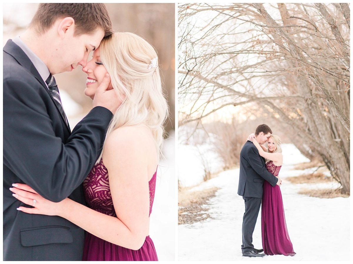 romantic engagement photos elegant in grande prairie alberta with chris and kaytlin with deep maroon dress and suit with the winter snow in the background and creamy caved in trees at muskoseepi park