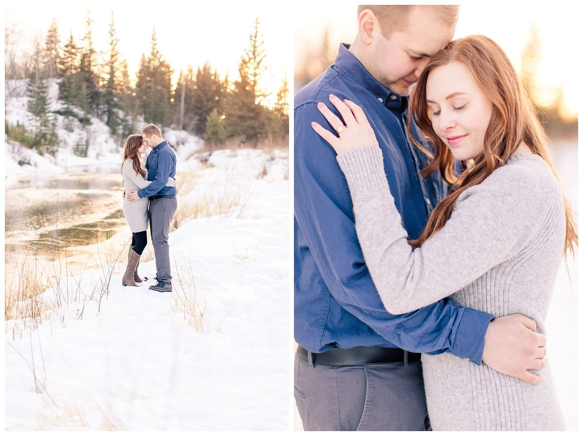 grande prairie wedding engagement photos with photographer beside the river with sunset glowing in the background in the river orange and super sunny couple is chest to chest with snow and grass all around them