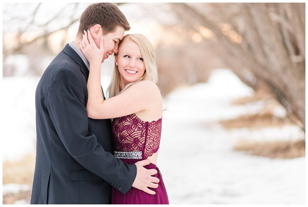 chris and kaytlin close up photo at their winter engagement session with kayla lynn photography groom nuzzle with lots of snow in the background and gorgeous creamy light