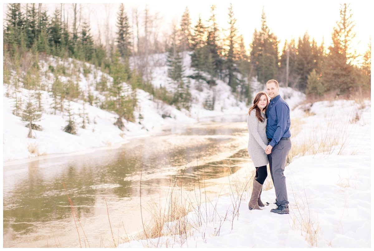 steven and gina by the south bear creek river with sun reflecting in the water in t he winter with all the snow and spruce trees in the background