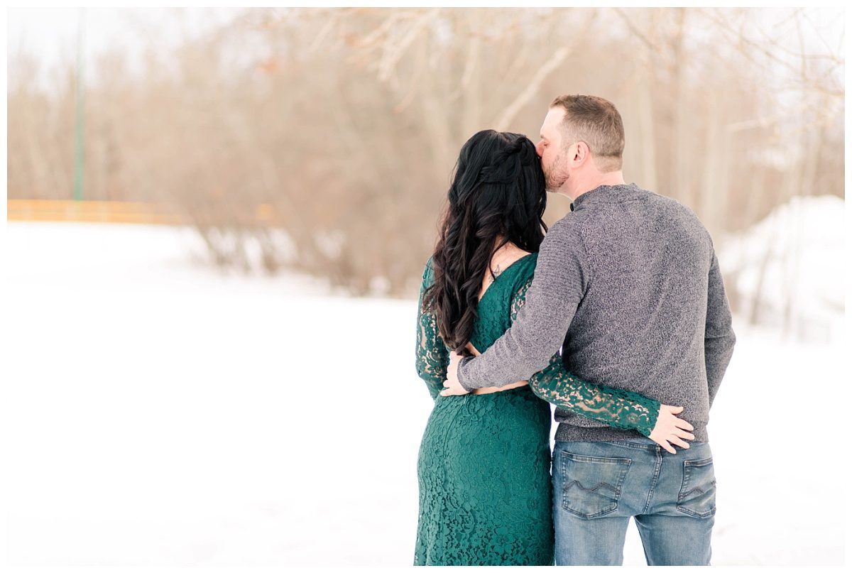 couple photos in the winter with arms around each others backs wearing emerald green lulus dress corwin kissing her forhead