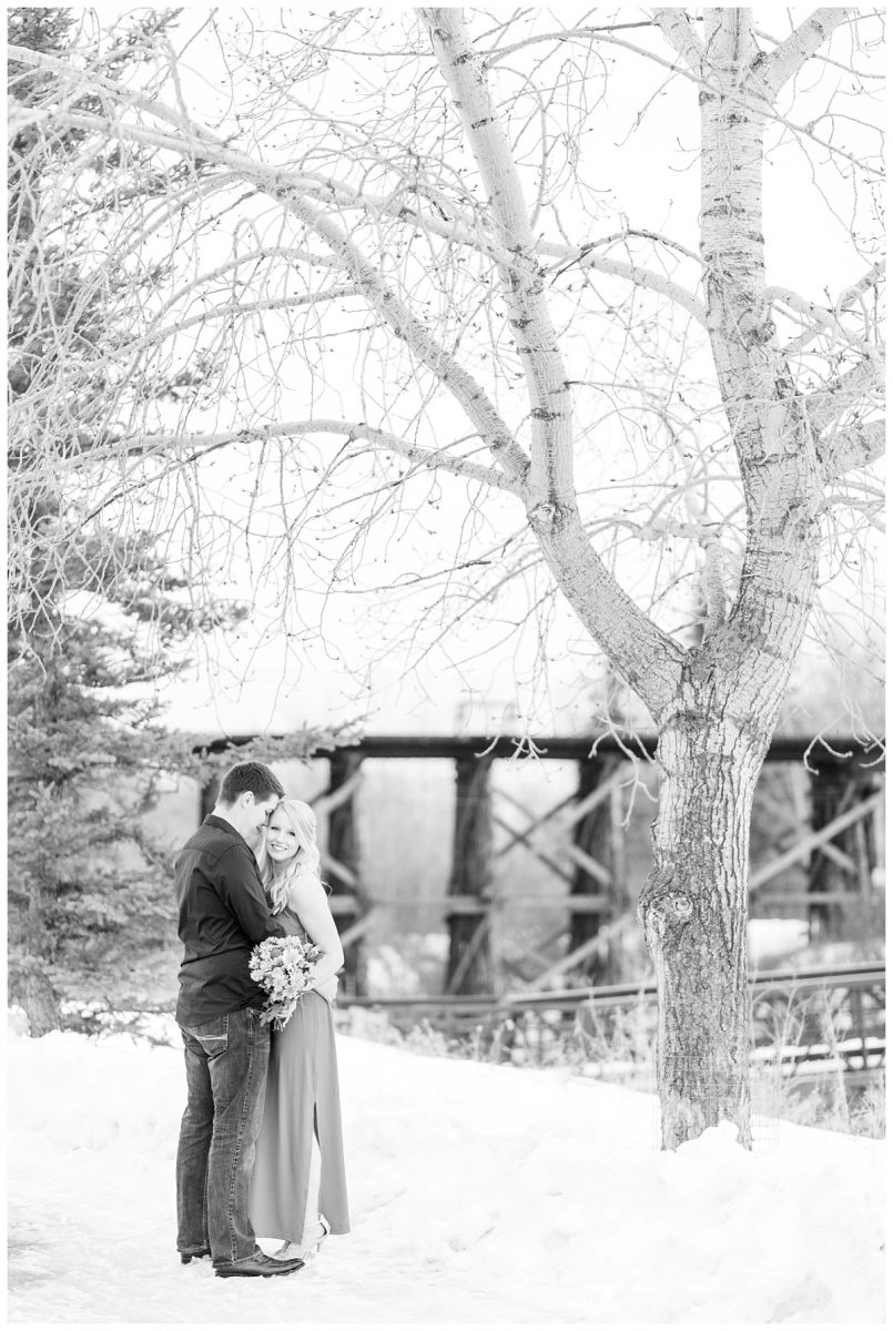 chris and kaytlin at their engagement session in grande prairie black and white photo next to a tree in front of the muskoseepi bridge in grande prairie alberta with their wedding photographer