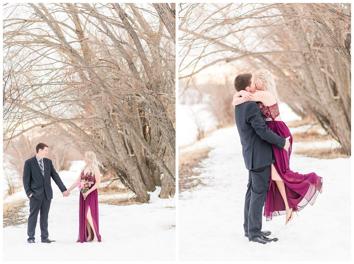 grande prairie wedding photographer captures chris and kaytlin along winter path full of snow in grande prairie alberta holding hands and kissing in the air
