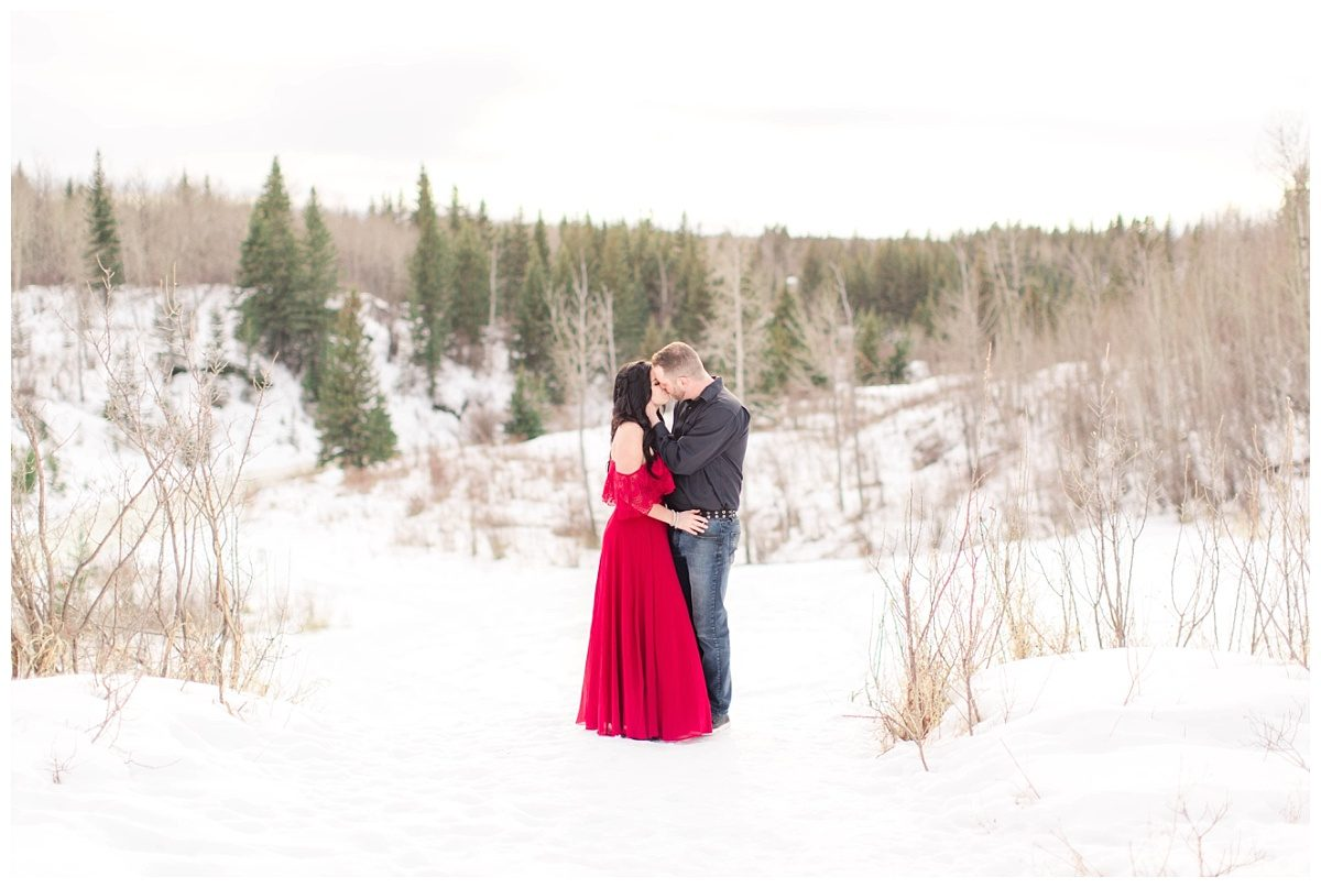 wide angle landscape photo of cute adorable couple kissing at the south bear creek hill with red dress
