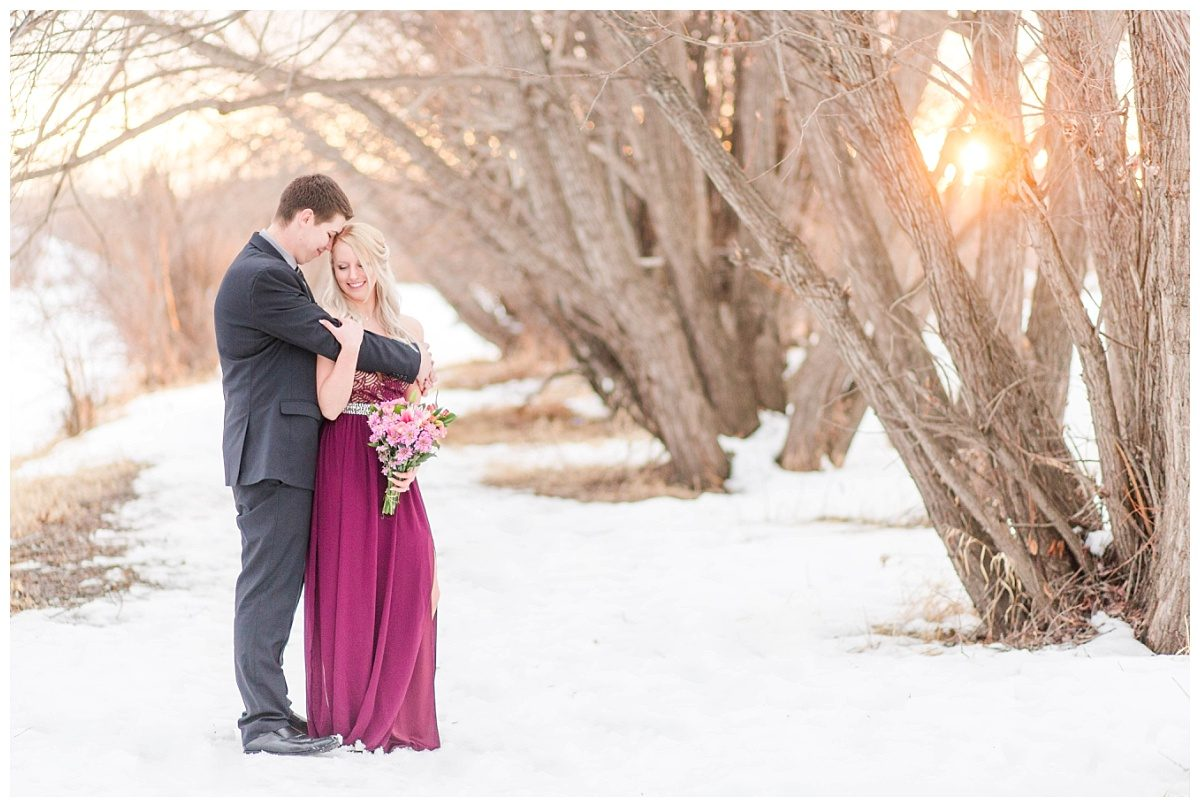 engagement photos with chris and kaytlin at sunset in the winter with lots of snow and sunset glow it looks super magical with maroon dress from le chateau professional wedding photographer alberta