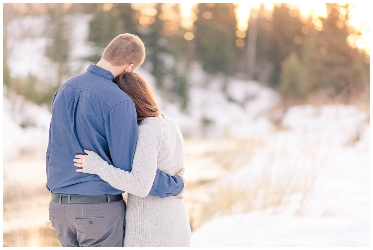 engagement couple in grande prairie putting arms around each other looking at the sunset outside in the snow beside the river