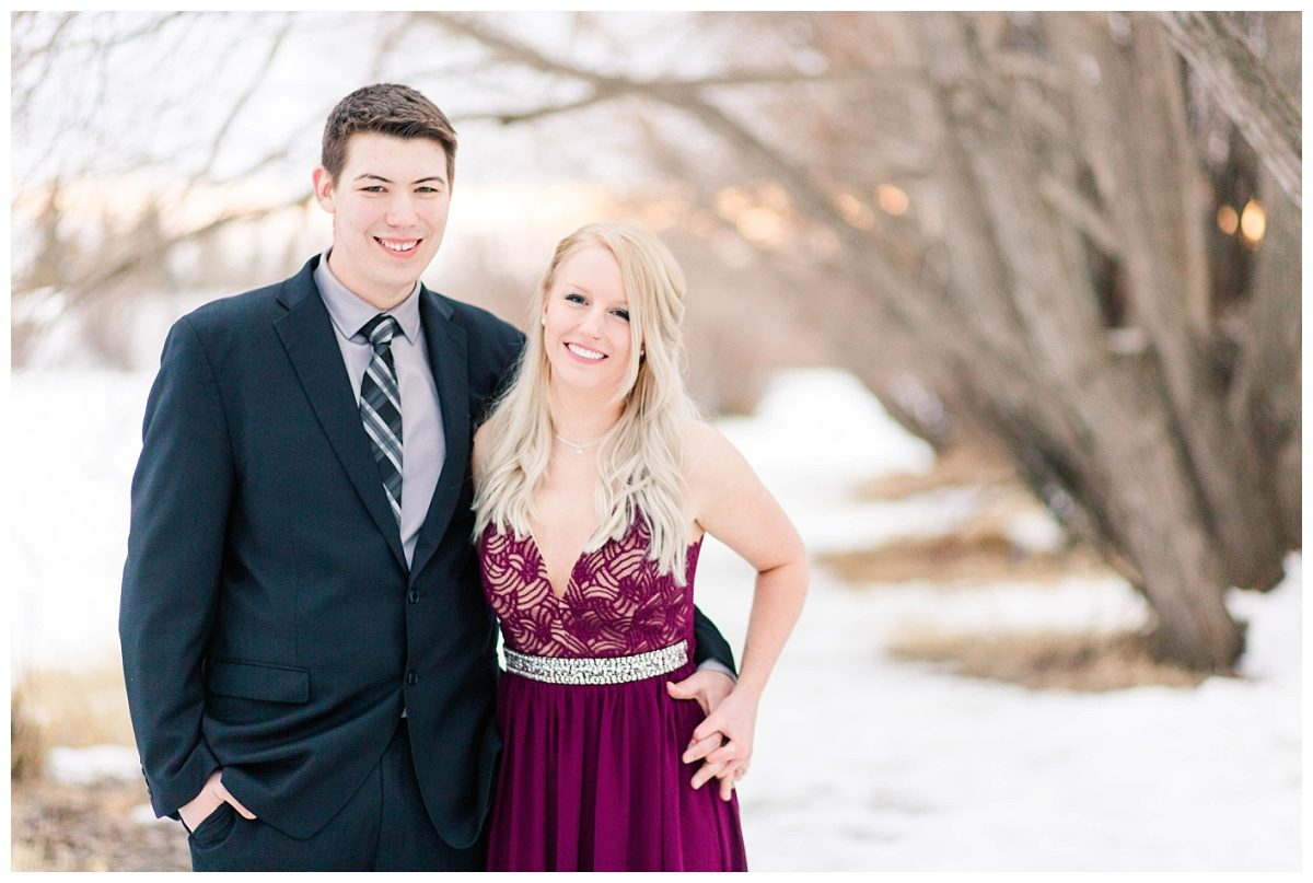 happy engaged couple mwith winter photos with snow in the background close up of them smiling at the camera in dress and suit elegant and fancy