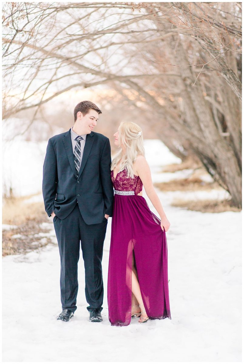 engaged couple wearing dress and suit in grande prairie alberta for their photos in the winter with maxi dress