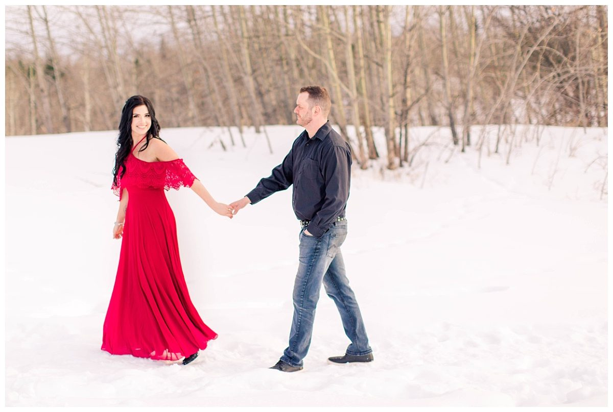 amanda and corwin couple engagment in the snow winter walking with red dress and jeans