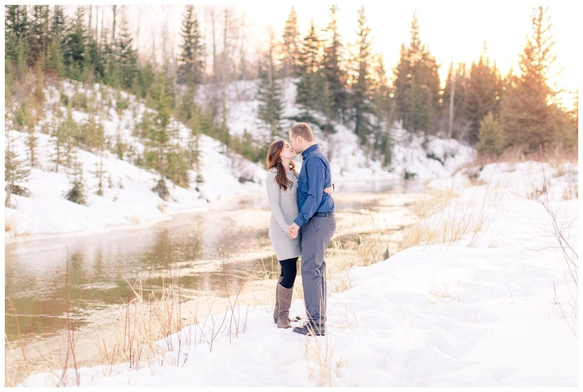 steven and gina nose to nose for their engagement photos with lots of winter snow and sunset glow in the background in the river at the south bear creek with lots of spruce trees in the background backdrop